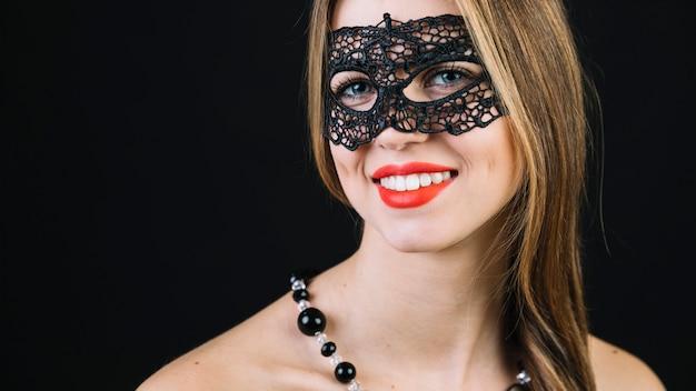 Close-up van een prachtige lachende vrouw in zwarte carnaval masker Gratis Foto