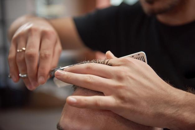 Close-up van een professionele kapper bijgesneden met een schaar en kam terwijl hij een kapsel aan zijn cliënt gaf. Gratis Foto