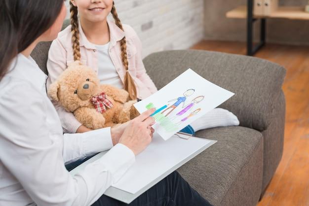 Close-up van een professionele psycholoog die familietekening bekijken die door een meisje met teddybear wordt getrokken Premium Foto