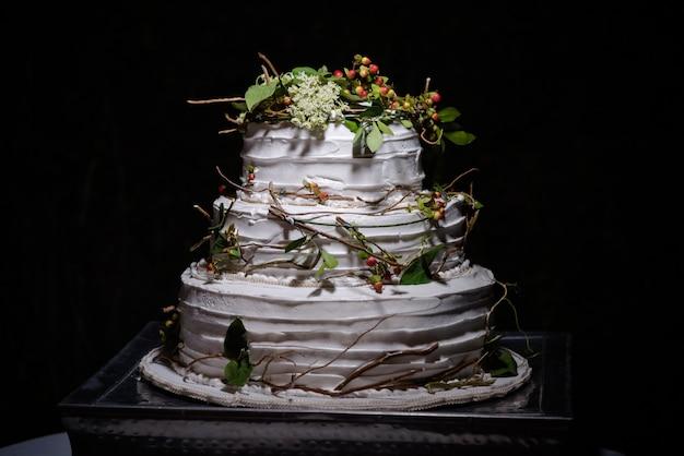 Close-up van een rustieke bruidstaart met groene bladeren, takken en kleine ronde bessen Gratis Foto