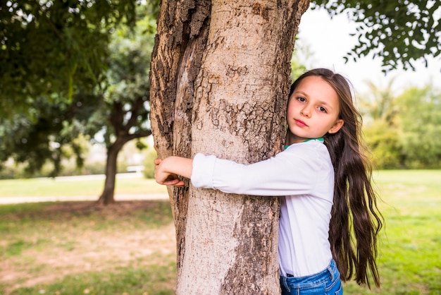 Close-up van een schattig meisje die boomboomstam koesteren Gratis Foto