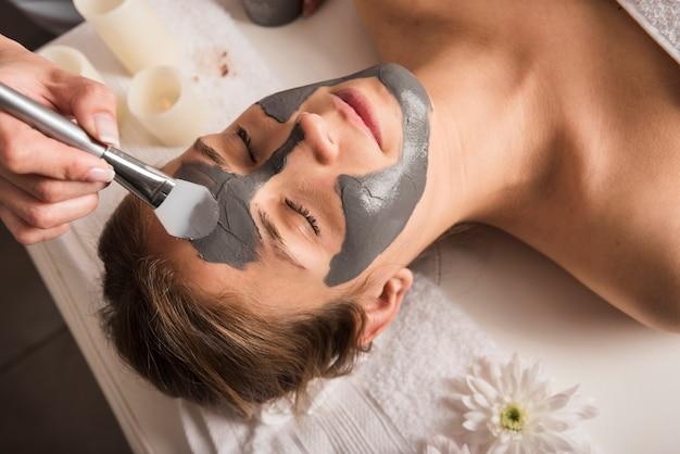 Close-up van een schoonheidsspecialist die gezichtsmasker op het gezicht van de vrouw toepast Gratis Foto