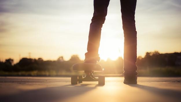 Close-up van een skateboarder omringd door bomen onder het zonlicht tijdens de zonsondergang Gratis Foto