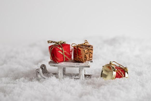 Close-up van een slee en kleurrijke geschenkdozen in de sneeuw, kerstmisspeelgoed op de witte achtergrond Gratis Foto