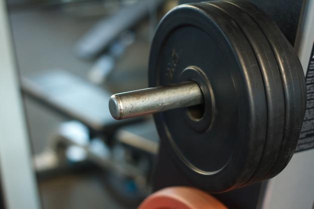 Close-up van een staaf met gewichten in een sportschool, achtergrond of concept van het gewichtheffen en sport Premium Foto