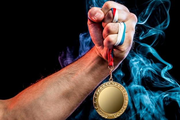 Close-up van een sterke mannelijke hand die een gouden medaille voor een sportieve prestatie houdt Premium Foto