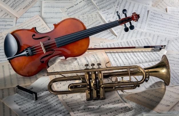 Close-up van een viool en een trompet op notitiebladen onder de lichten Gratis Foto
