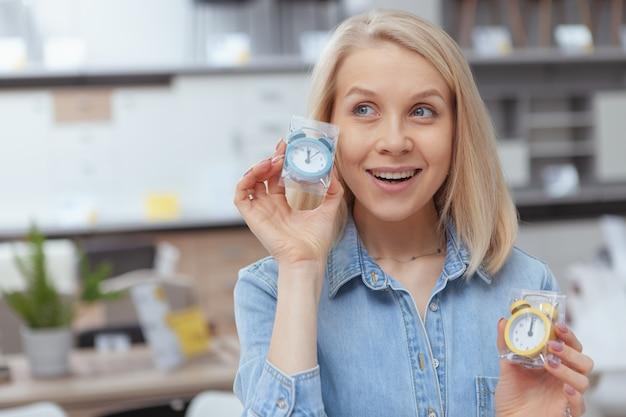 Close up van een vrolijke aantrekkelijke vrouw met twee schattige kleine wekkers, glimlachend opgewonden Premium Foto