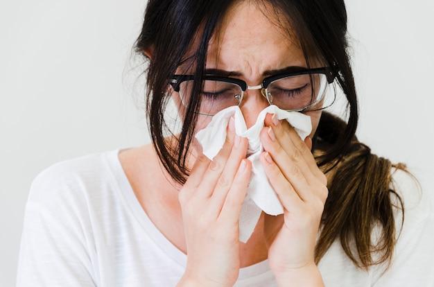 Close-up van een vrouw die haar neus in papieren zakdoekje blaast tegen witte achtergrond Gratis Foto