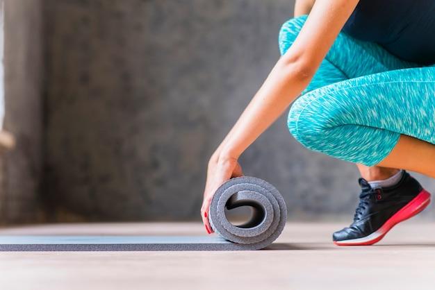 Close-up van een vrouw die yogamat vouwt Gratis Foto