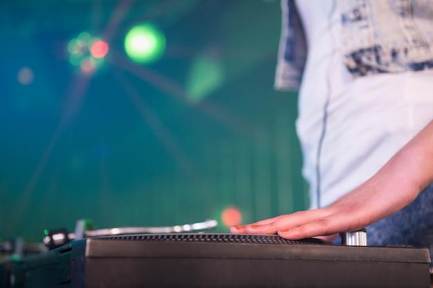 Close-up van een vrouwelijke dj-hand op een record in nachtclub Premium Foto