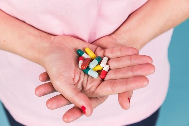 Close-up van een vrouwelijke hand met capsule in de hand Gratis Foto