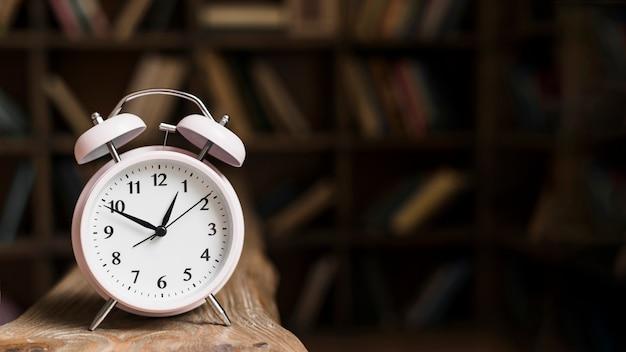 Close-up van een wekker op houten bureau Premium Foto