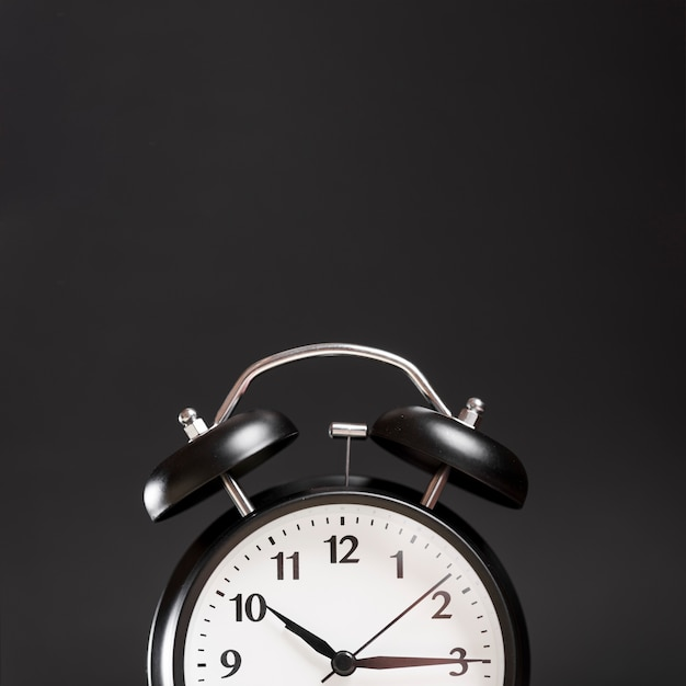 Close-up van een wekker tegen zwarte achtergrond Gratis Foto