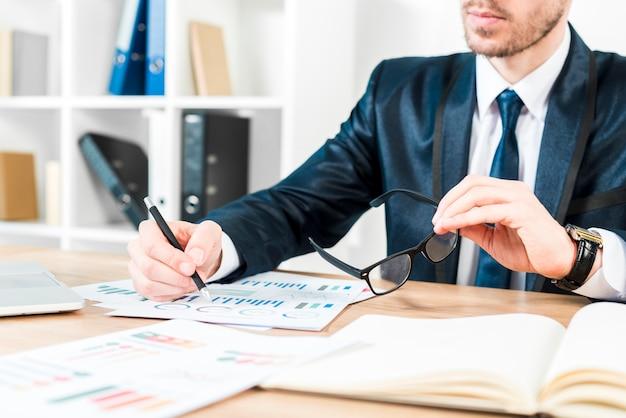 Close-up van een zakenman die de in hand oogglazen van de grafiekholding analyseert Gratis Foto