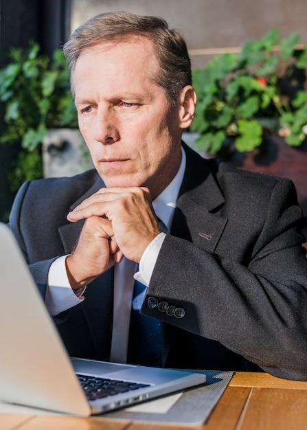 Close-up van een zakenman die laptop het scherm bekijkt Gratis Foto