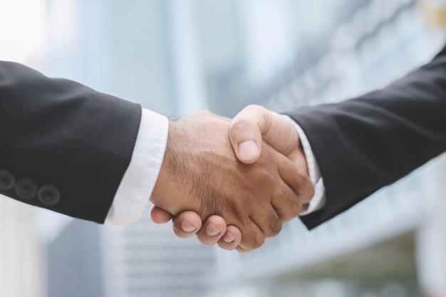 Close-up van een zakenman hand schudden investeerder tussen twee collega's ok, slagen in het bedrijfsleven holding hands. Premium Foto