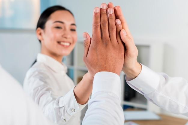 Close-up van een zakenvrouw high-five te geven aan zijn zakelijke partners Gratis Foto