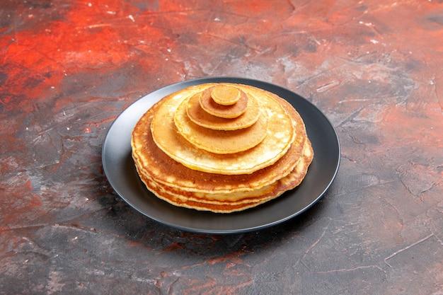Close-up van eenvoudige zelfgemaakte pannenkoeken in een zwarte plaat Gratis Foto