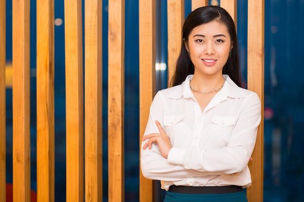 Close-up van elegante aziatische dame bij houten partitie Gratis Foto