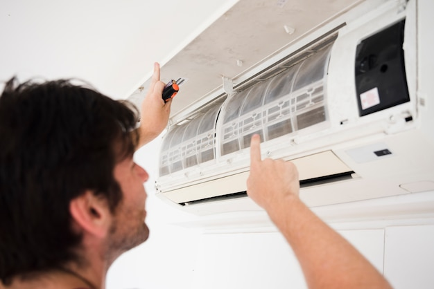 Close-up van elektricien die airconditioner herstelt Gratis Foto