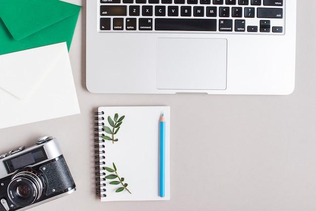 Close-up van enveloppen; vintage camera; spiraal notitieblok; gekleurd blauw potlood en laptop op grijze achtergrond Gratis Foto