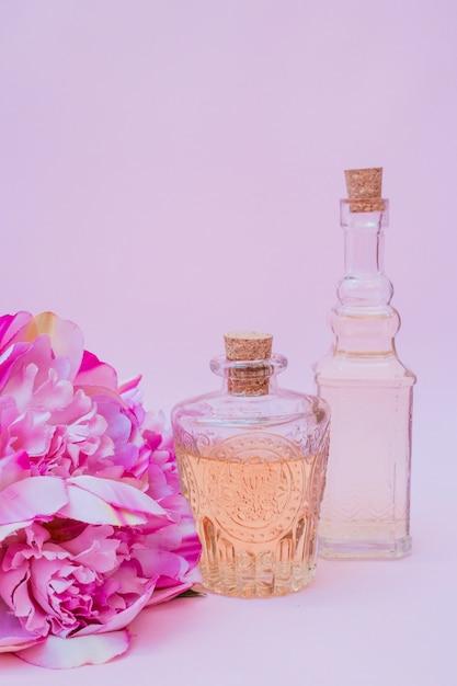 Close-up van etherische olieflessen en bloemen op purpere achtergrond Premium Foto