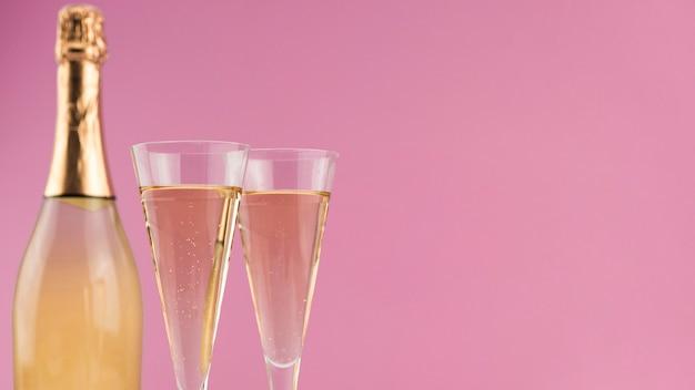 Close-up van fles champagne met glazen en exemplaarruimte Gratis Foto