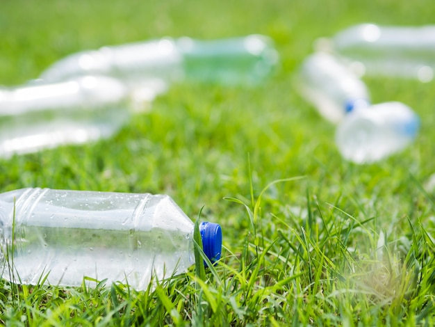 Close-up van fles van het afval de plastic water op gras bij park Gratis Foto