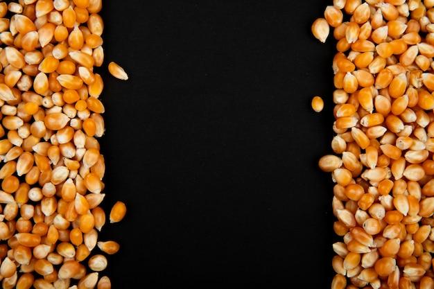 Close-up van gedroogde maïs zaden aan de linker- en rechterkant en een zwarte achtergrond met kopie ruimte Gratis Foto