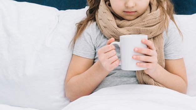 Close-up van geduldig meisje met sjaal rond haar hals die witte koffiemok houdt Gratis Foto