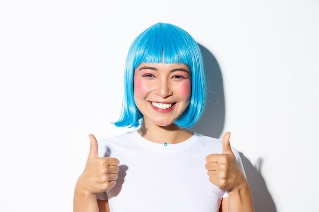Close-up van gelukkig aziatisch meisje in blauwe pruik, glimlachend en thumbs-up in goedkeuring tonen Gratis Foto