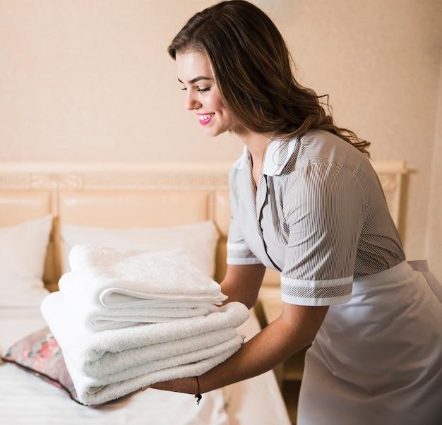Close-up van gelukkig kamermeisje brengen stapel van verse witte badhanddoeken op het bed Gratis Foto