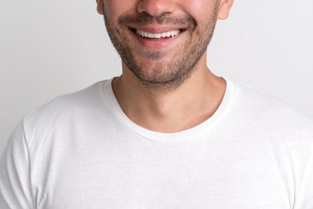 Close-up van gelukkige stoppels jonge man tegen witte achtergrond Gratis Foto
