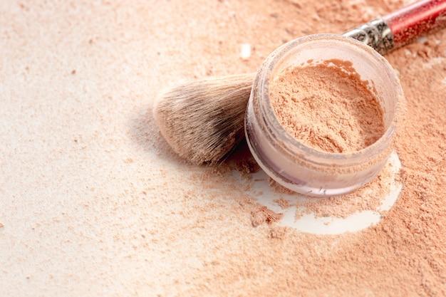 Close-up van gemalen minerale flikkering poeder gouden kleur met make-up borstel Gratis Foto
