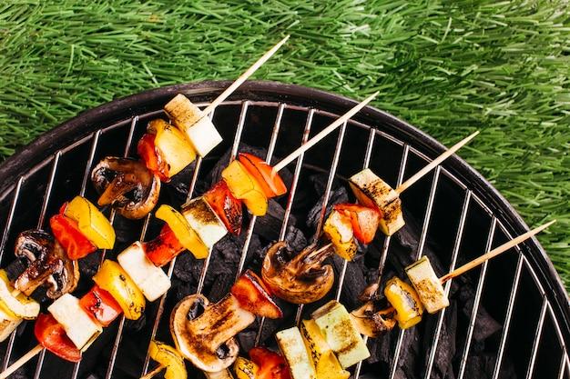 Close-up van geroosterde vleespennen met vlees en groente bij de grill over groene grasmat Gratis Foto