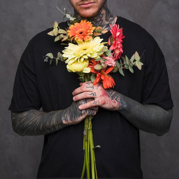 Close-up van getatoeeerde jonge man hand met bloemen boeket in de hand tegen de grijze muur Gratis Foto