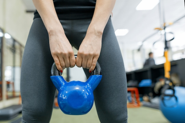Close-up van gewicht in de handen van een sportieve vrouw Premium Foto