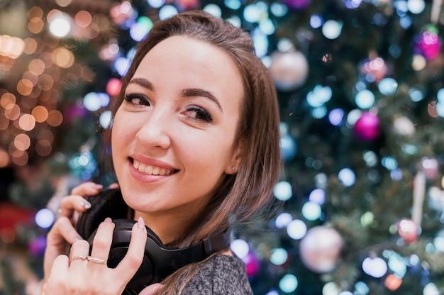Close-up van glimlachend wijfje die hoofdtelefoons dragen dichtbij kerstmisboom die weg eruit zien Gratis Foto