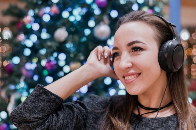 Close-up van glimlachend wijfje die hoofdtelefoons dragen dichtbij kerstmisboom Gratis Foto