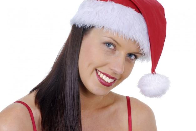 Close-up van glimlachende jonge volwassen vrouw met de rode die hoed van kerstmissanta op wit wordt geïsoleerd Gratis Foto