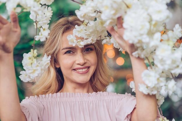 Close-up van glimlachende jonge vrouw die door witte bloemen kijkt Gratis Foto