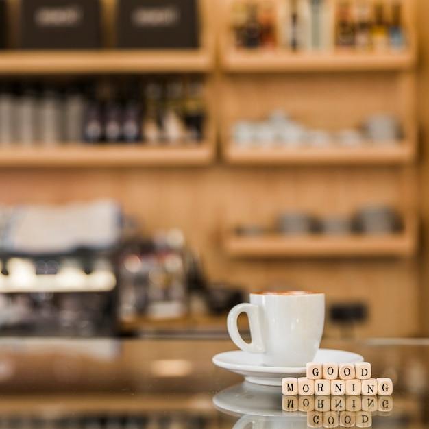 Close-up van goedemorgen houten blokken met kop van koffie op glaskabinet Gratis Foto