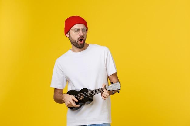 Close-up van grappige jonge man een gitaar spelen. geïsoleerd op geel goud Premium Foto