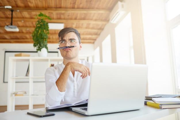 Close-up van grappige peinzende jonge zakenman draagt een wit overhemd op kantoor Gratis Foto
