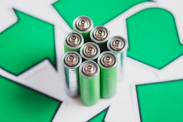 Close-up van groene batterijen met recycle pictogram op witte achtergrond Gratis Foto