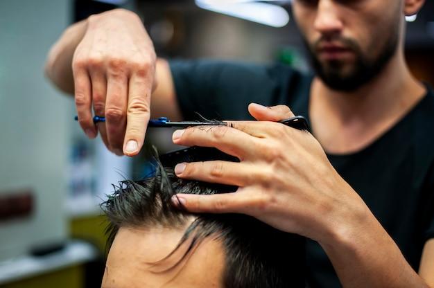Close-up van haarstylist die klantenhaar snijden Gratis Foto