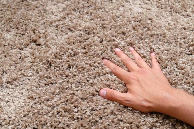 Close-up van hand aanraken van zacht tapijt. zacht en donzig tapijt. Premium Foto