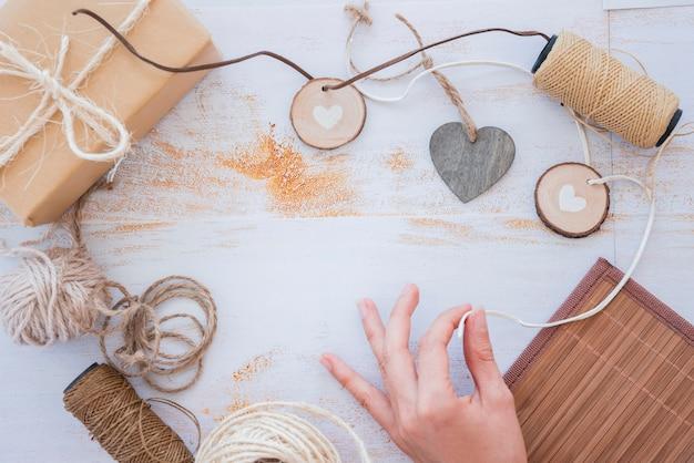 Close-up van hand die hartslinger met spoel en verpakte giftdoos op wit bureau maakt Gratis Foto