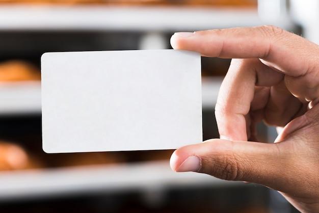 Close-up van hand die leeg wit rechthoekig visitekaartje houdt Gratis Foto